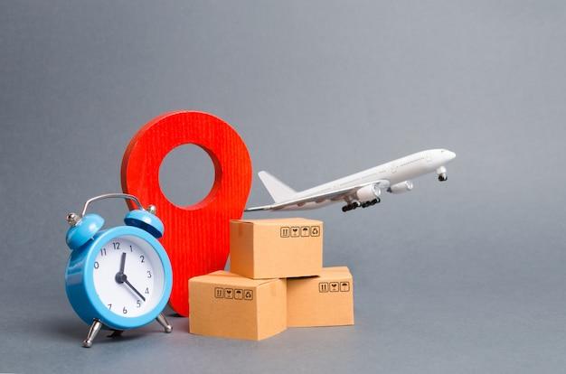 Avión y pila de cajas de cartón, pin de posición rojo y despertador azul. Foto Premium