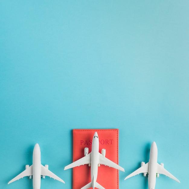 Aviones de juguete y pasaporte sobre fondo azul Foto Premium