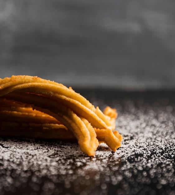 Azúcar y churros en primer plano de una mesa Foto gratis