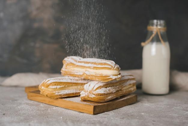 Azúcar espolvoreando en eclair sobre la tabla de cortar Foto gratis
