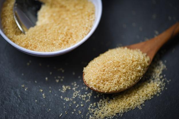 Azúcar marrón en cuchara de madera en negro oscuro con azúcar de caña en un tazón blanco Foto Premium