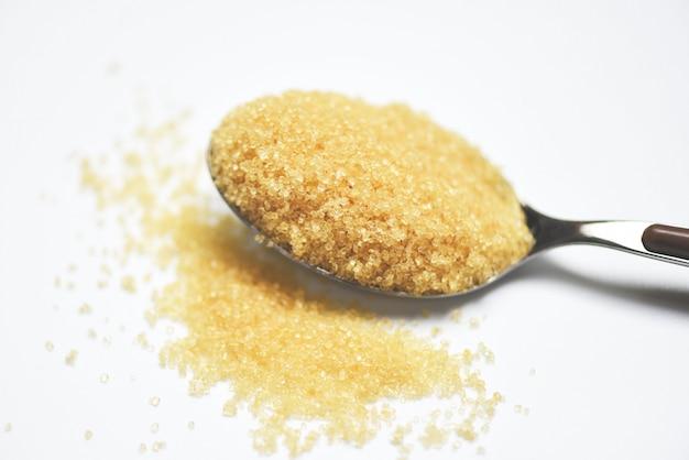 Azúcar moreno en una cuchara en blanco Foto Premium
