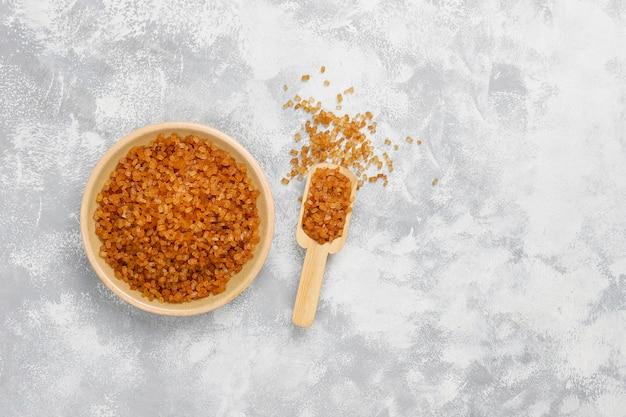 Azúcar moreno en placa de cerámica sobre hormigón, vista superior Foto gratis