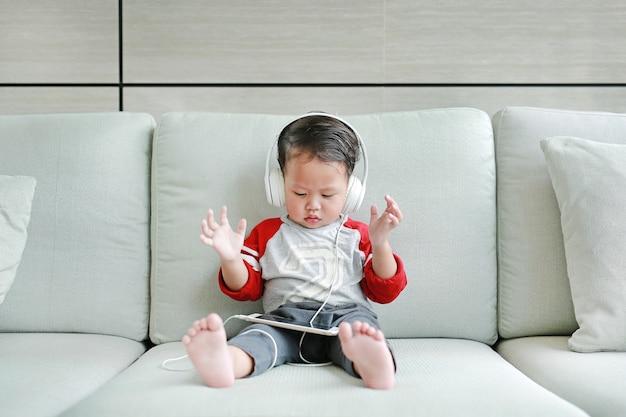 Baby boy escuchando música con auriculares Foto Premium
