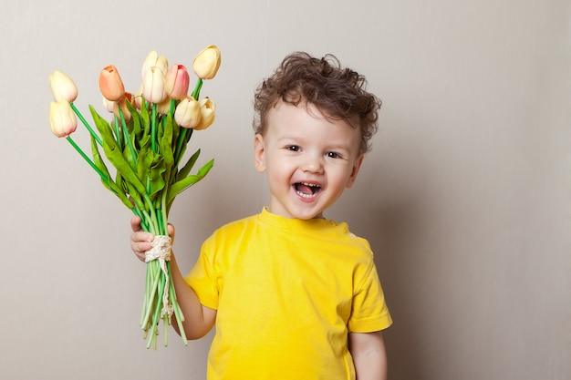 Baby boy riendo entre tulipanes rosados Foto Premium