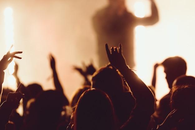 Bailando en un concierto mientras la cantante actúa rodeada de luces Foto gratis