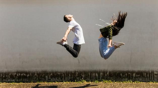 Bailarín saltando en el aire contra la pared gris Foto gratis