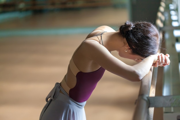 Bailarina de ballet clásico en barre en sala de ensayo Foto gratis
