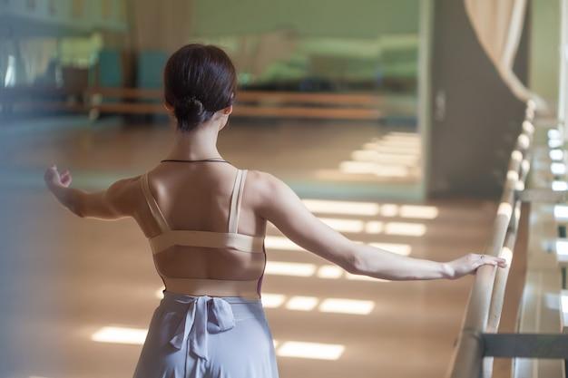 Bailarina de ballet clásico posando en barre en sala de ensayo Foto gratis