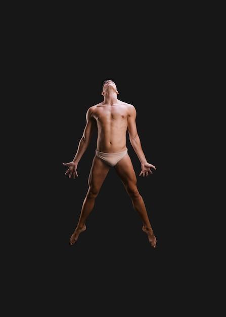Bailarina sin camisa saltando durante la actuación Foto gratis
