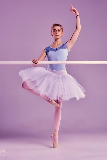 Bailarina clásica posando en la barra de ballet Foto gratis
