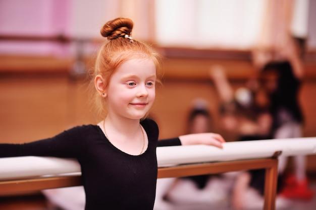 Bailarina linda chica pelirroja estirando y haciendo las divisiones Foto Premium