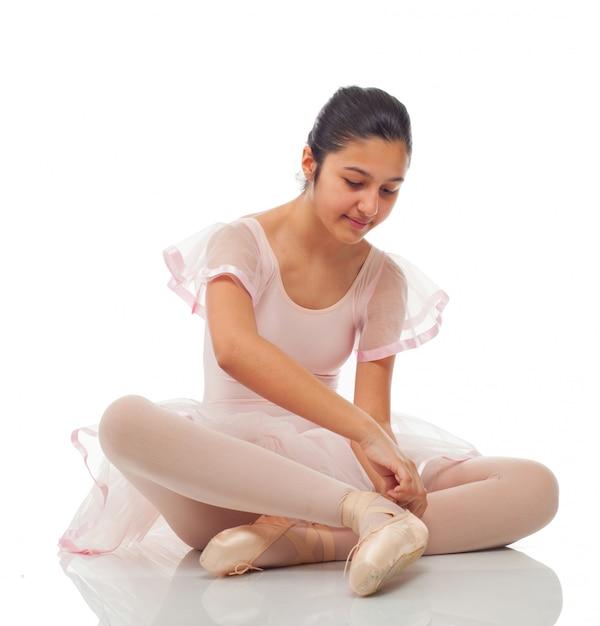 Bailarina mientras se ata los zapatos para bailar. Foto Premium