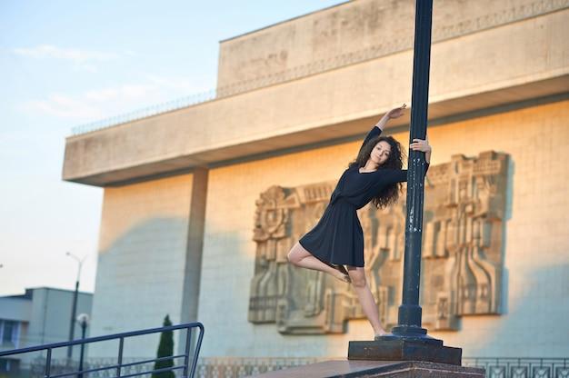 Bailarina en el pilar de la lámpara cerca de la fachada del edificio interesante. Foto gratis