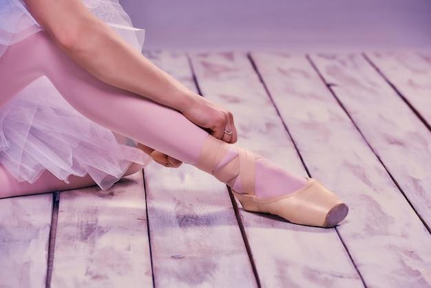 Bailarina profesional poniéndose sus zapatos de ballet Foto gratis