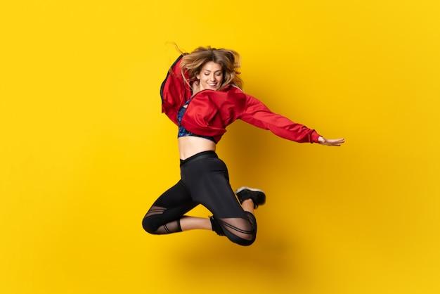 Bailarina urbana bailando sobre amarillo aislado y saltando. Foto Premium