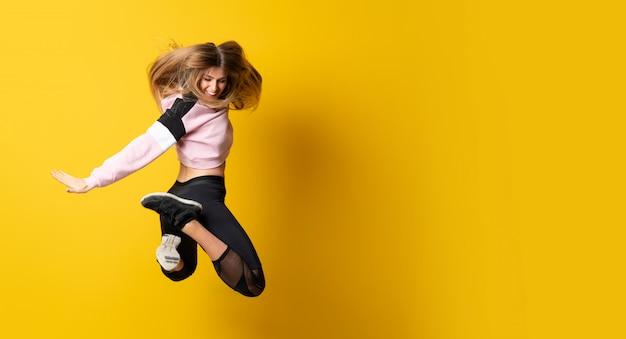 Bailarina urbana bailando sobre fondo amarillo aislado y saltando Foto Premium