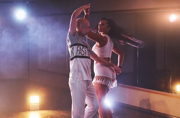 Bailarines expertos actuando en el cuarto oscuro bajo la luz del concierto y el humo. sensual pareja realizando una danza contemporánea artística y emocional Foto gratis
