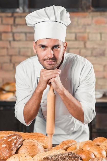 Baker apoyado en un rodillo sobre la mesa con variedad de panes Foto gratis