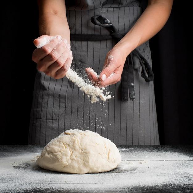 Baker vertiendo harina sobre la masa Foto gratis