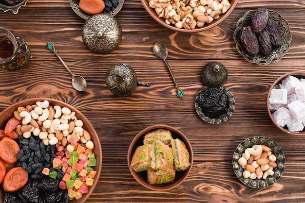 Baklava de postre turco de ramadan; lukum; fechas; frutos secos y nueces en cuencos de barro y metálicos contra el escritorio de madera Foto gratis