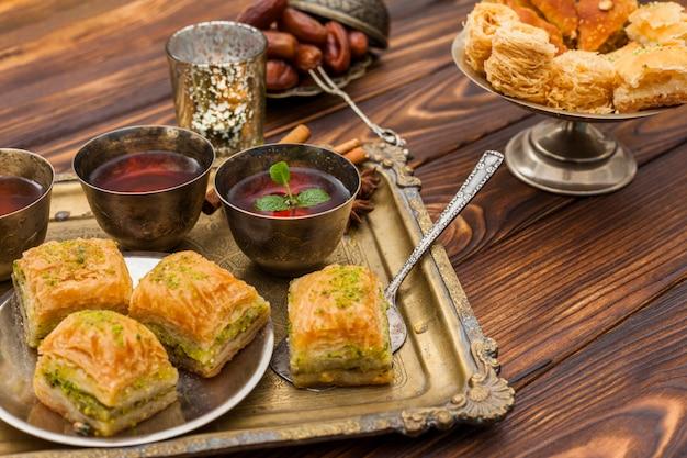 Baklava con tazas de té en la bandeja Foto gratis