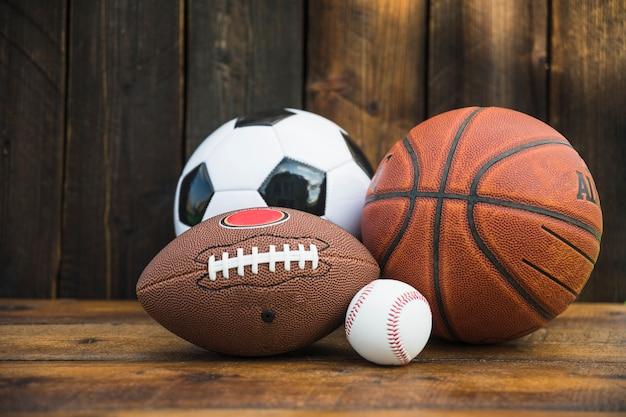 Balón de fútbol; béisbol; rugby y baloncesto en mesa de madera Foto Premium