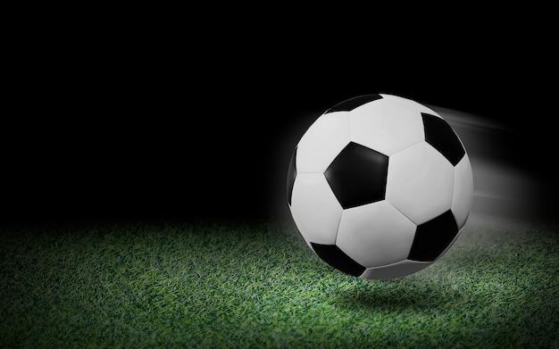 Balón de fútbol sobre hierba verde y fondo negro Foto Premium