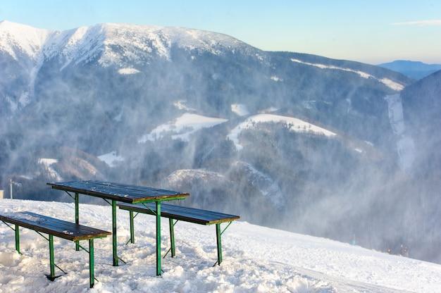 Bancos y la mesa en la cima de una montaña con una hermosa vista sobre una escena de invierno con montañas, árboles y nieve. Foto Premium