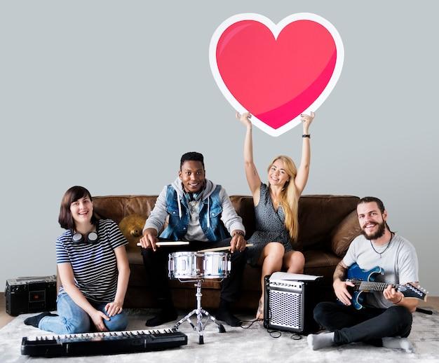 Banda de músicos sosteniendo un emoticono de corazón. Foto gratis