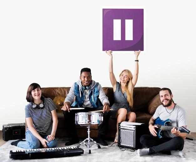 Banda de músicos sosteniendo un icono de botón de pausa Foto gratis