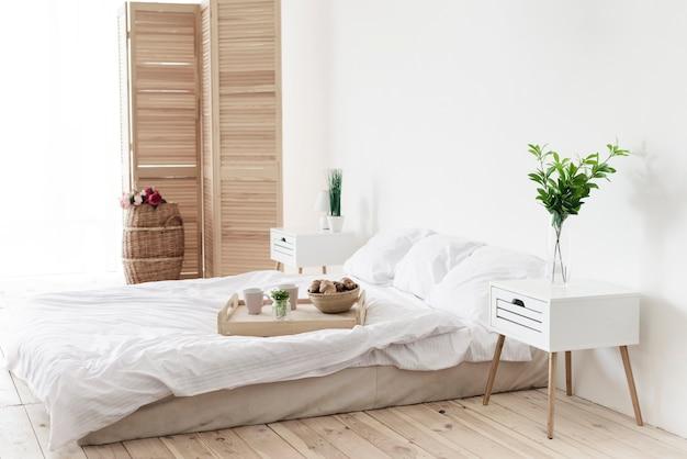 Bandeja con desayuno en cama en habitación luminosa. Foto gratis