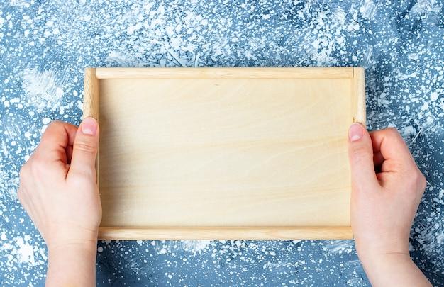 Bandeja de madera vacía en manos femeninas, vista superior Foto Premium
