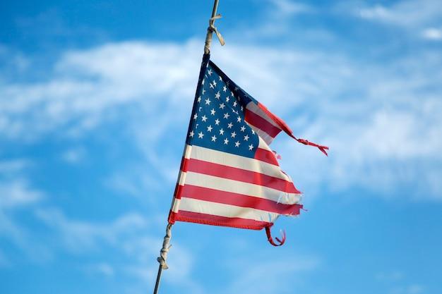 Bandera americana rota ondeando en el mástil   Foto Premium