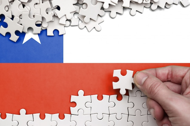 La bandera de chile está representada en una mesa en la que la mano humana dobla un rompecabezas de color blanco. Foto Premium