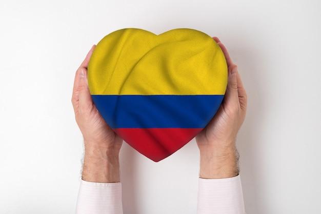 Bandera de colombia en una caja en forma de corazón en manos masculinas. Foto Premium