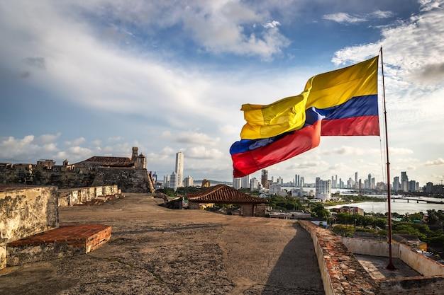 La bandera colombiana en el fuerte de cartagena en un día nublado y ventoso. cartagena, colombia Foto Premium
