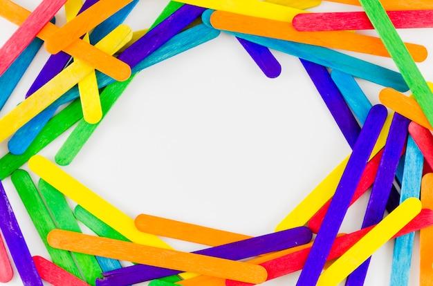 Bandera del día del orgullo lgbt con palos de colores Foto gratis