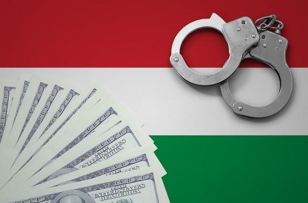 Bandera de hungría con esposas y un fajo de dólares. el concepto de operaciones bancarias ilegales en moneda estadounidense Foto Premium
