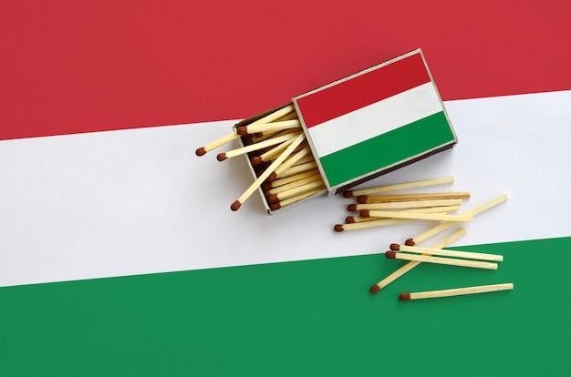 La bandera de hungría se muestra en una caja de fósforos abierta, de la que caen varios partidos y se encuentra en una bandera grande Foto Premium