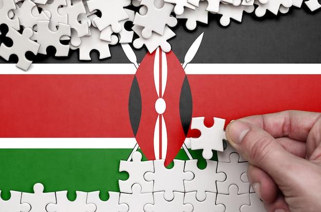 La bandera de kenia se representa en una mesa en la que la mano humana dobla un rompecabezas de color blanco. Foto Premium