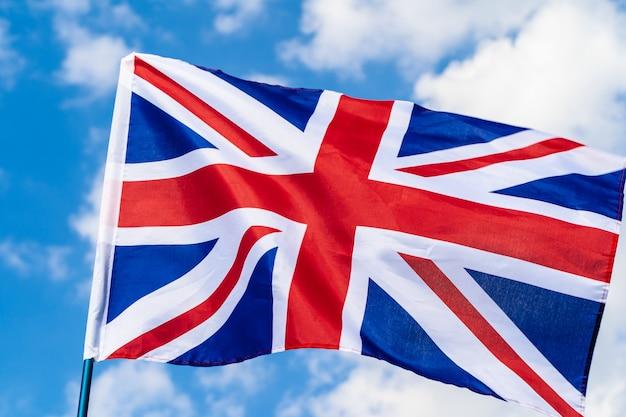 Bandera del reino unido ondeando en el viento en el cielo azul Foto Premium
