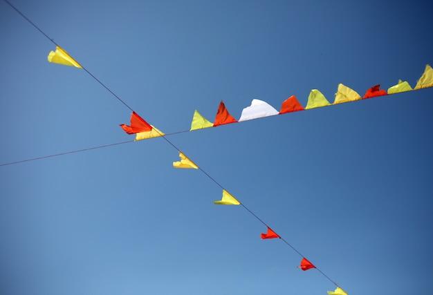 Banderas coloridas del festival de la calle, feria o fiesta contra el cielo azul. Foto Premium