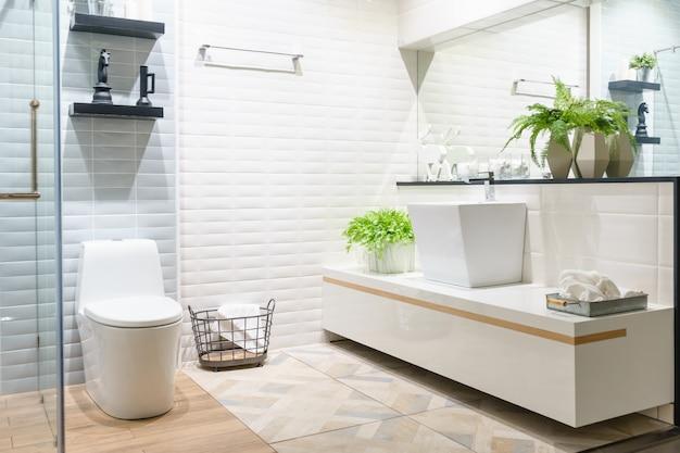 Baño amplio y moderno con azulejos brillantes con inodoro y lavabo. vista lateral Foto Premium