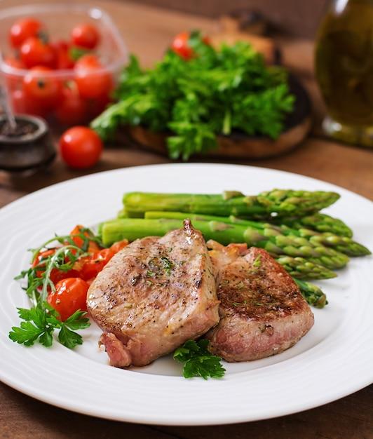 Barbacoa de carne de ternera a la parrilla con espárragos y tomates. Foto gratis