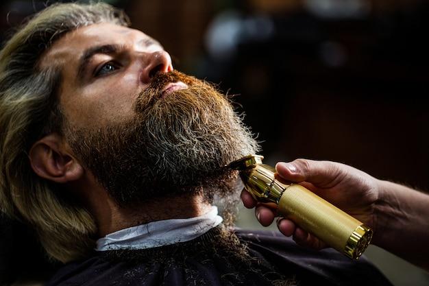 Barber trabaja con un cortapelos. cliente inconformista cortándose el pelo. manos de un peluquero con un cortapelos, primer plano. Foto Premium