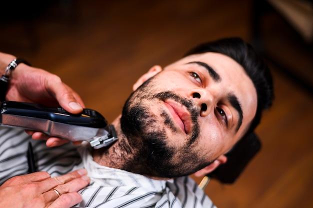 Barbero de alto ángulo que afeita la barba del cliente Foto gratis
