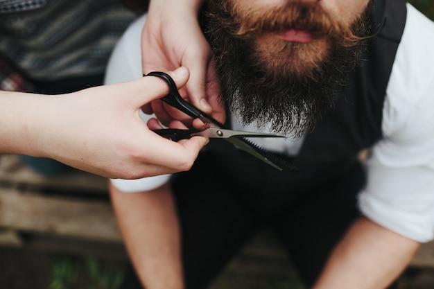 Barbero cortando una barba con tijeras Foto gratis