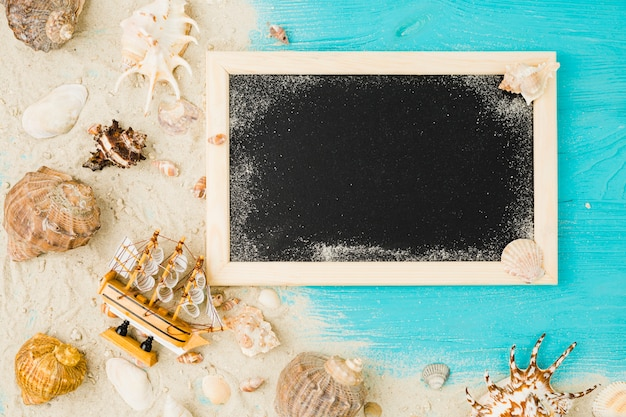Barco de juguete y conchas marinas entre la arena cerca de la pizarra Foto gratis