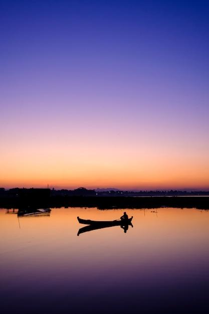Barco en el lago al atardecer Foto gratis